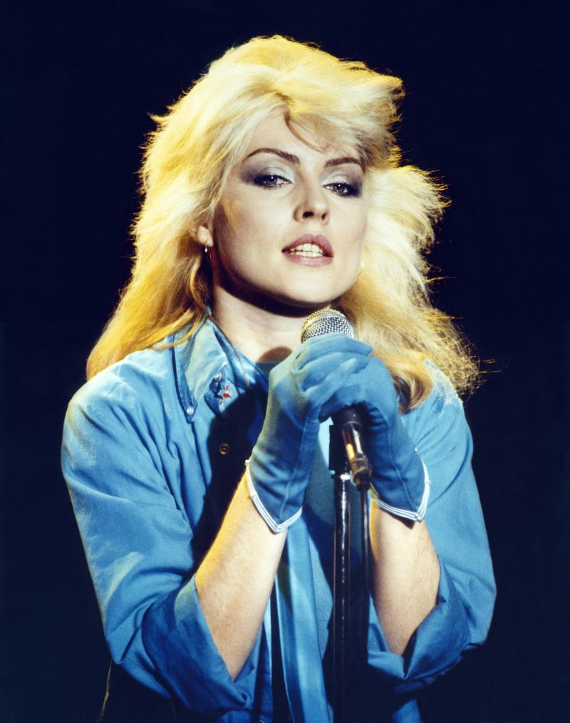 Debbie Harry wears blue top and gloves while performing with Blondie in London, 1978.