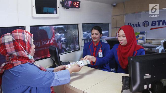 Seorang wanita menukarkan uang pecahan kecil pada mobil kas keliling Bank BTN di Lapangan IRTI Monas, Jakarta, Rabu (7/6). Bank Indonesia bekerja sama dengan 13 bank lainnya melayani penukaran uang hingga 16 Juni mendatang. (Liputan6.com/Angga Yuniar)