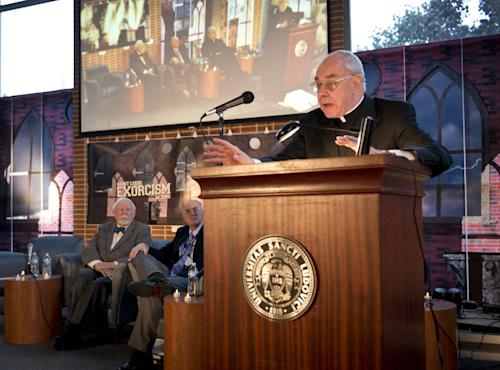 In this photo provided by St. Louis University, the Rev. John Padberg, S.J., director of the Institute of Jesuit Sources, speaks during a panel discussion at St. Louis University in St. Louis, Tuesday, Oct. 29, 2013, about the month-long 1949 demon-purging ritual at the school's former Alexian Brothers Hospital. The treatment of an unidentified suburban Washington, D.C., boy formed the basis for the 1971 novel by William Peter Blatty, The Exorcist, and the film of the same name two years later. Listening from left to right, are: Thomas B. Allen, author of Possessed: The True Story of an Exorcism, and John Waide, archivist at Saint Louis University. (AP Photo/St. Louis University, Michelle Peltier)