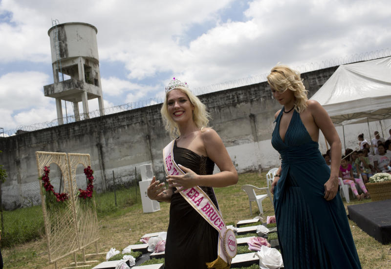 Inmate Veronica Verone, 25, left, smiles after she was crowned Miss Talavera Bruce 2018, at the penitentiary the beauty pageant is named for, in Rio de Janeiro, Brazil, Tuesday, Dec. 4, 2018. Authorities say they organize the pageant, which attracts a lot of local media attention, to help the prisoners with their self-esteem and promote integration between them. (AP Photo/Silvia Izquierdo)