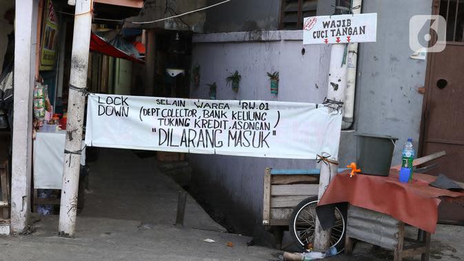 Spanduk penutupan akses masuk terpasang di salah satu gang yang ditutup secara mandiri di kawasan Tambora, Jakarta, Sabtu (4/4/2020). Penutupan akses masuk kawasan ini untuk membatasi kegiatan warga dan mencegah penyebaran serta penularan virus COVID-19. (Liputan6.com/Helmi Fithriansyah)