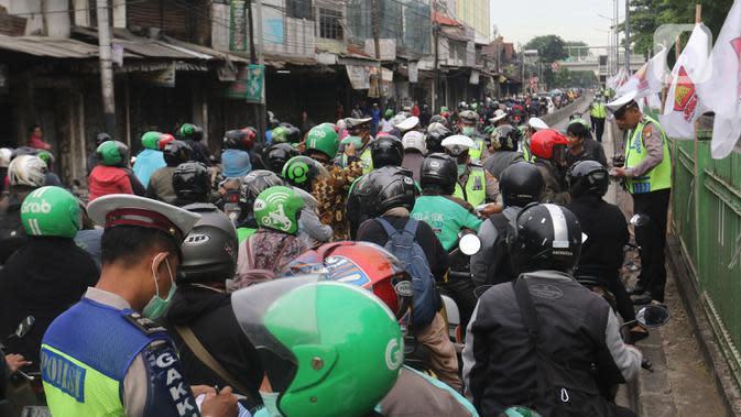 Polisi menilang pengendara sepeda motor yang menerobos jalur Transjakarta di Jalan Sultan Agung, Manggarai, Jakarta, Rabu (12/2/2020). Pengendara kerap melintasi jalur Transjakarta untuk menghindari kemacetan lalu lintas. (Liputan6.com/Herman Zakharia)