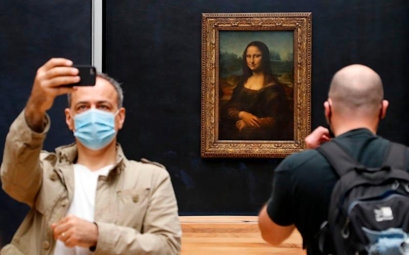 """A visitor wearing a face mask takes a selfie in front of Leonardo da Vinci's masterpiece """"Mona Lisa"""" at the Louvre Museum in Paris on July 6, 2020, on the museum's reopening day - FRANCOIS GUILLOT/AFP"""
