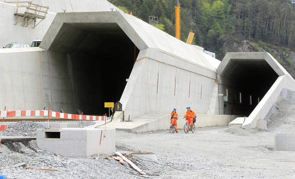 Workers cycle past the northern entrances of the NEAT Gotthard Base tunnel near Erstfeld