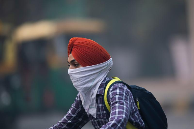 A motorist covering up his face rides along a street in smoggy conditions in New Delhi on Nov. 1, 2019. (Photo: Jewel Samad/AFP via Getty Images)