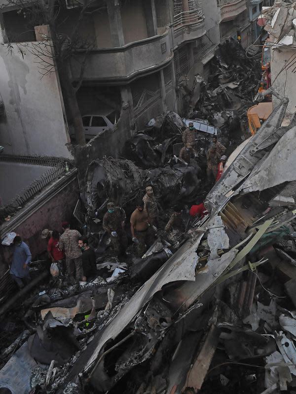 Petugas keamanan mencari korban di puing pesawat Pakistan International Airlines yang jatuh di Karachi, Pakistan, Jumat (22/5/2020). Menurut Direktur Utama PIA Arshad Mahmood Malik, satu-satunya penumpang yang selamat adalah Presiden Bank Punjab, Zafar Masud. (Asif HASSAN/AFP)
