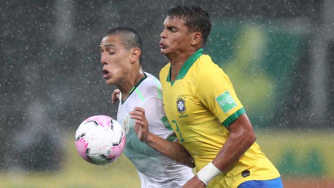 Bek Brasil, Thiago Silva, berebut bola dengan penyerang Bolivia, Cesar Menacho, pada laga kualifikasi Piala Dunia 2020 di Corinthians Arena, Sabtu (10/10/2020) pagi WIB. Brasil menang 5-0 atas Bolivia. (AFP/Buda Mendes/pool)
