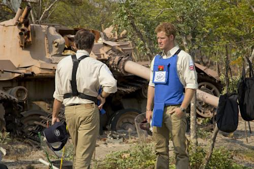 In this handout photo made available by the HALO Trust on Saturday, Aug. 17, 2013, Britain's Prince Harry, right, speaks with HALO Director Guy Willougby as they stand near a South African Olifant tank destroyed in the Battle of Cuito Cuanavale in 1988, in Angola. Harry returned from Angola, where he visited a landmine clearance charity championed by his late mother, Princess Diana. The HALO Trust charity said Saturday the 28-year-old prince visited the Angolan town of Cuito Cuanavale, which saw heavy fighting during the southern African nation's 1975-2002 civil war. The group said Harry toured minefields and met beneficiaries of the group's work. (AP Photo/HALO Trust)