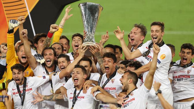 Para pemain Sevilla berselebrasi memegang trofi setelah menang atas Inter Milan pada pertandingan Final Liga Europa di Stadion Rhein Energie, Sabtu (22/8/2020) dini hari. Sevilla menjadi juara Liga Europa setelah menang dengan skor 3-2. (Lars Baron, Pool Photo via AP)