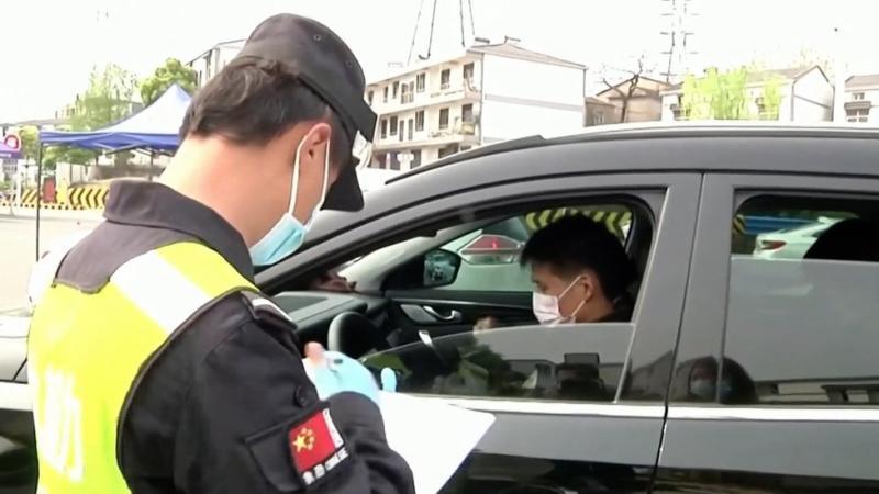 Polisi China mengawasi warga yang keluar masuk.