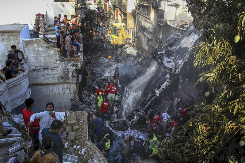 Volunteers look for survivors of a plane that crashed in a residential area of Karachi, Pakistan, May 22, 2020. An aviation official says a passenger plane belonging to state-run Pakistan International Airlines crashed near Karachi's airport. (AP Photo/Fareed Khan)