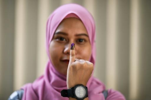 Voters dip their finger in halal ink after casting their ballot, like this Indonesian woman shown after advance overseas voting in Malaysia