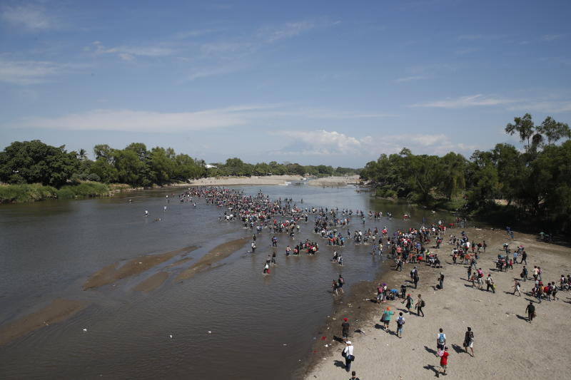 Central American migrants cross the Suchiate River by foot from Tecun Uman, Guatemala, to Mexico, Monday, Jan. 20, 2020. More than a thousand Central American migrants hoping to reach United States marooned in Guatemala are walking en masse across a river leading to Mexico in an attempt to convince authorities there to allow them passage through the country. (AP Photo/Moises Castillo)