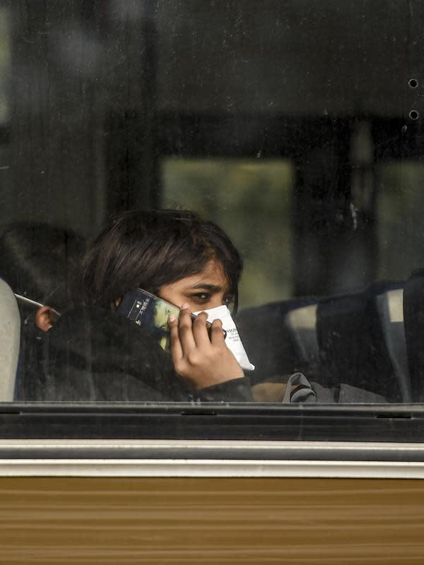 Seorang wanita India berada di dalam bus saat keluar dari Bandara Internasional Indira Gandhi setelah dievakuasi dari kota Wuhan di China, di New Delhi (1/2/2020). Jumlah total kematian akibat wabah virus corona di China tercatat mencapai 259 hingga Jumat (31/1/2020). (AFP/Money Sharma)