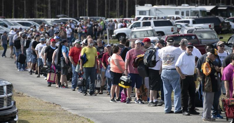 """In this Saturday, May 23, 2020 photo, hundreds of race fans wait in line to purchase tickets at the Ace Speedway on in the rural Alamance County community of Altamahaw near Elon, N.C. North Carolina Gov. Roy Cooper's administration has ordered closed a small stock-car track that's allowed large crowds to gather repeatedly for weekend races well above COVID-19 limits for mass gatherings. Cooper's health secretary says Ace Speedway in Alamance County is an """"imminent hazard"""" for the virus' spread and can't reopen unless it creates a safety plan to keep fans away. (Robert Willett/The News & Observer via AP)"""