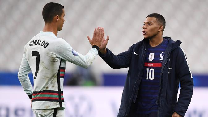 Striker Portugal, Cristiano Ronaldo, berbincang dengan striker Prancis, Kylian Mbappe, usai laga UEFA Nations League di Stadion Stade de France, Senin (12/10/2020). Kedua tim bermain imbang 0-0. (AFP/Franck Fife)