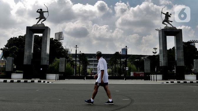Seorang pria dengan mengenakan masker berolahraga selama pemberlakuan Pembatasan Sosial Berskala Besar (PSBB) di Kawasan Senayan, Jakarta, Kamis (16/4/2020). Kendati Kawasan Senayan pun juga diterapkan PSBB, warga bisa tetap berolahraga di Komplek Gelora Bung Karno (GBK). (Liputan6.com/Johan Tallo)