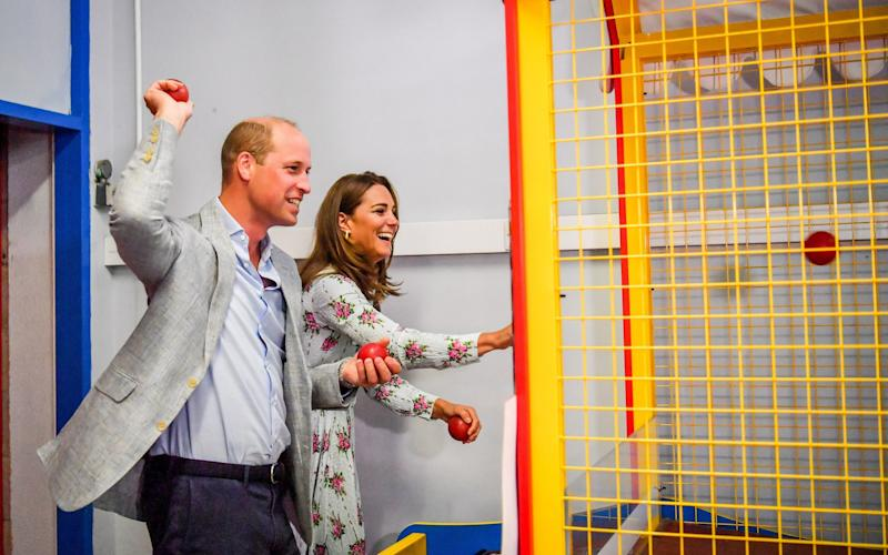 The Duke and Duchess of Cambridge throw balls on an arcade game in Barry Island, South Wales - Ben Birchall/PA