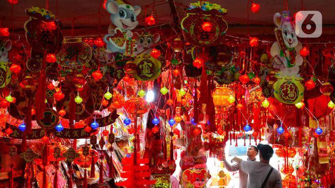 Calon pembeli memilih pernak-pernik Imlek yang dijual di kawasan Glodok, Jakarta, Senin (13/1/2020). Menurut pedagang setempat, menjelang tahun baru Imlek pada 25 Januari mendatang terjadi peningkatan penjualan pernak-pernik dan hiasan hingga 3 kali lipat. (merdeka.com/Arie Basuki)