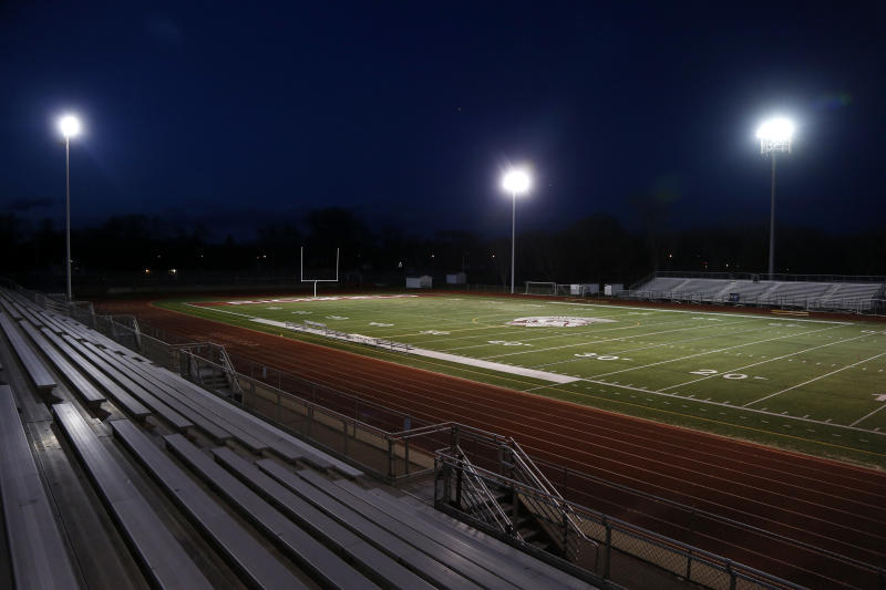The lights shine on an empty football stadium at Richfield High School Wednesday night, April 8, 2020, in Richfield, Minn. Seeking to brighten spirits amid the virus outbreak, the symbolic act of turning on the lights became a movement — fueled by social media with the hashtag #BeTheLight — across the country.  (AP Photo/Jim Mone)