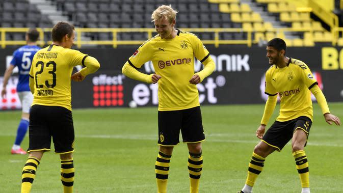 Pemain Borussia Dortmund merayakan gol yang dicetak oleh Thorgan Hazard ke gawang Schalke 04 pada laga Bundesliga di Stadion Signal Iduna Park, Sabtu (16/5/2020). Pandemi COVID-19 membuat pemain melakukan selebrasi jaga jarak. (AP/Martin Meissner)