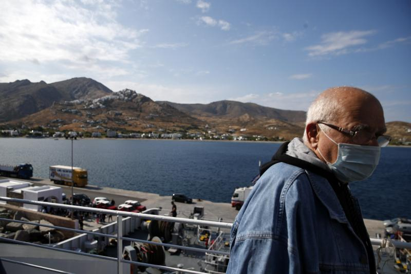 A passenger wearing a face mask to prevent the spread of the new coronavirus, stands on the deck of a ferry as it approaches the Aegean Sea island of Serifos, Greece, on Tuesday, May 26, 2020.  Greece restarted regular ferry services to its islands Monday, and cafes and restaurants were also back open for business as the country accelerated efforts to salvage its tourism season. (AP Photo/Thanassis Stavrakis)