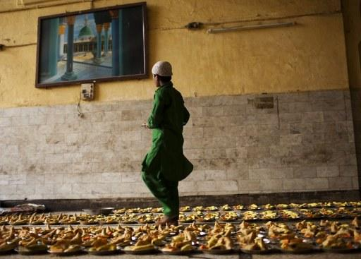 An Indian Muslim prepares food to handout to devotees so they can break their fast at sunset during  Ramadan at the shrine of 13th century Sufi Muslim saint Hazrat Nizamuddin Aulia in New Delhi on August 12, 2012. Islam's holy month of Ramadan is calculated on the sighting of the new moon and Muslims all over the world are supposed to fast from dawn to dusk during the month.  AFP PHOTO/ Andrew Caballero-Reynolds