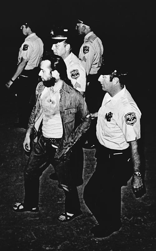 "FILE - In this Friday, July 22, 1972 file photo, Milwaukee Police officers lead comedian George Carlin off the Summerfest grounds in Milwaukee, Wis. He was arrested after his act which included ""The Seven Words You Can Never Say on Television,"" a social commentary about censorship. (AP Photo)"