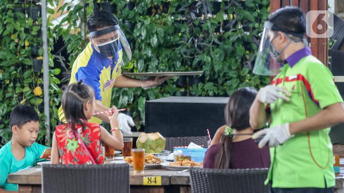 Pramusaji lengkap dengan APD berupa face shield, sarung tangan dan masker menyajikan makanan di Restoran Bandar Djakarta, Tangerang Selatan, Rabu (10/6/2020). Perpanjangan PSBB Tangerang Raya hingga 15 Juni guna menekan penyebaran virus Covid-19 menjelang new normal. (Liputan6.com/Fery Pradolo)