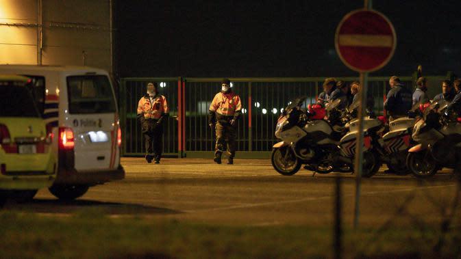 Petugas kemanan berjaga saat pesawat yang membawa penumpang dari Wuhan tiba di bandara militer di Melsbroek, Belgia, Minggu (2/2/2020). Belgia memulangkan warganya dari Wuhan menyusul wabah virus corona di kota tersebut. (NICOLAS MAETERLINCK/Belga/AFP)