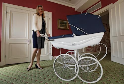 In this Tuesday, April 30, 2013 photo, Lucinda Croft, the managing director of Dragons, a small British family business that was also tapped to design nurseries for British royals, poses for the photographer as she pushes a pram while she showcases a hotel nursery suite at a central London hotel. Britain's Prince William and Kate, formally known as the Duchess of Cambridge, plan to move into apartments at London's Kensington Palace soon after the baby is born in July. Few will ever get a glimpse inside the room where the future British monarch will grow up, but the designers hired by late Princess Diana to create her sons' William and Harry's nursery at the palace can offer some expert hints.(AP Photo/Lefteris Pitarakis)