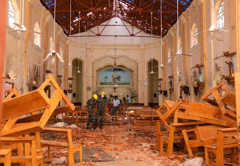Sri Lankan military officers conduct inspections inside the St. Sebastians church where a bomb blast took place. Source: Getty