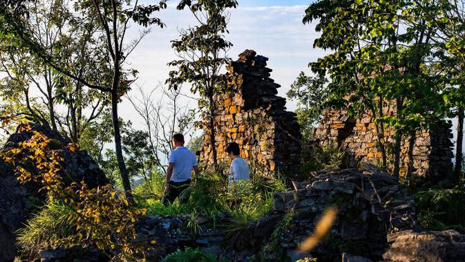 Para wisatawan mengunjungi peninggalan kompleks desa kuno di Minzhu, sebuah kota di Wilayah Langao, Provinsi Shaanxi, China pada 29 Juni 2020. Terletak di daerah pegunungan di Gunung Bashan, peninggalan kompleks desa tersebut berasal dari masa Dinasti Ming (1368-1644). (Xinhua/Tao Ming)