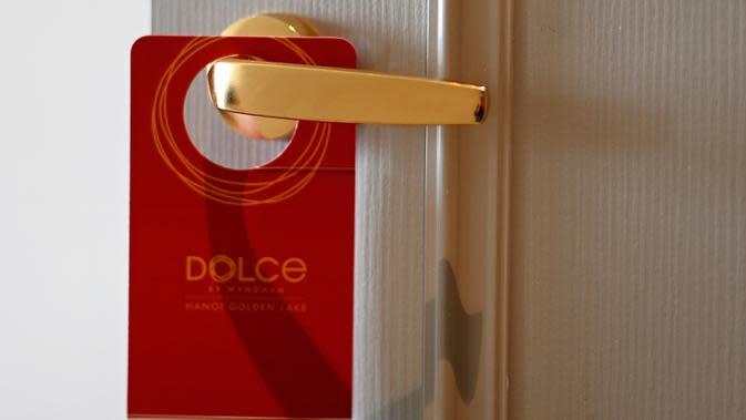 Sebuah plakat tergantung pada gagang pintu kamar hotel Dolce Hanoi Golden Lake yang baru saja diresmikan di Hanoi, Vietnam pada Kamis (2/7/2020). Hotel tersebut merupakan hotel berlapiskan emas 24 karat pertama di dunia. (Manan VATSYAYANA / AFP)