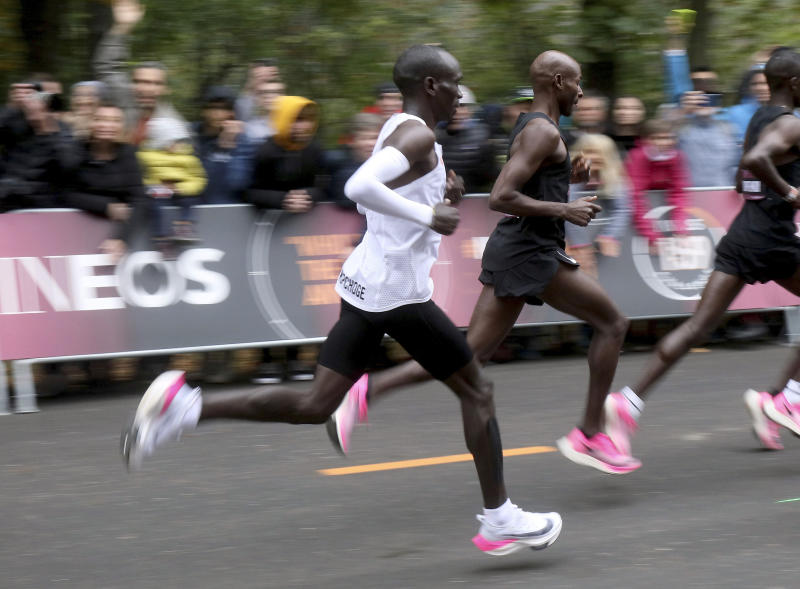 In this Oct. 12, 2019 photo, marathon runner Eliud Kipchoge from Kenya, white vest, wearing Nike AlphaFly prototype running shoe, and his pacemaking team, wearing pink Nike Vaporfly shoes, run during the INEOS 1:59 Challenge attempt to run a sub two-hour marathon in Vienna, Austria. Nike has a new racing shoe; The Air Zoom Alphafly Next%, which was unveiled at a flashy fashion show in New York on Wednesday night, Feb. 5, 2020. Kipchoge wore a prototype of the shoe when he ran the world's first sub-2-hour marathon in an unofficial race in October.  (AP Photo/Ronald Zak, File)