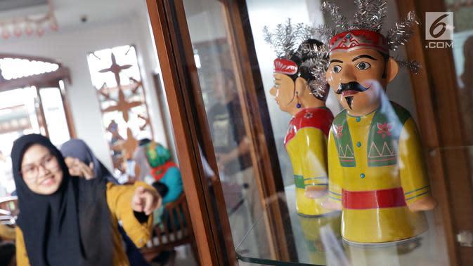 Pengunjung melihat-lihat miniatur ondel-ondel yang dipajang di Museum Betawi, kawasan Setu Babakan, Jakarta, Minggu (23/6/2019). Dalam rangka perayaan HUT ke-492 Jakarta beragam acara kebudayaan khas betawi digelar di kawasan Setu Babakan, Jakarta. (Liputan6.com/Helmi Fithriansyah)
