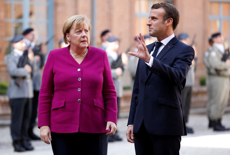 FILE PHOTO: French President Emmanuel Macron welcomes German Chancellor Angela Merkel before a joint Franco-German cabinet meeting in Toulouse