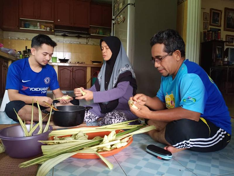 Mohd Sobri Mohd Noor (right) making ketupat with his wife Nor Aslin Jaafar and son Muhammad Najmi Mohd Sobri.