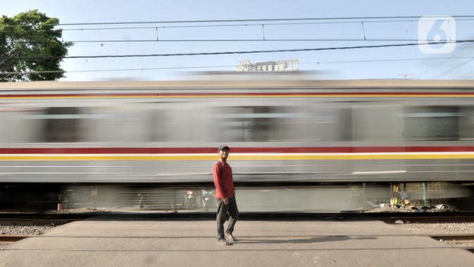 Penjaga perlintasan berdiri saat kereta melintas di Jalan Duri Kosambi Raya, Jakarta, Rabu (15/1/2020). Warga setempat membangun palang secara swadaya dan mengatur lalu lintas karena belum dipasangnya palang pintu otomatis perlintasan kereta dekat Stasiun Rawa Buaya itu. (merdeka.com/Iqbal Nugroho)