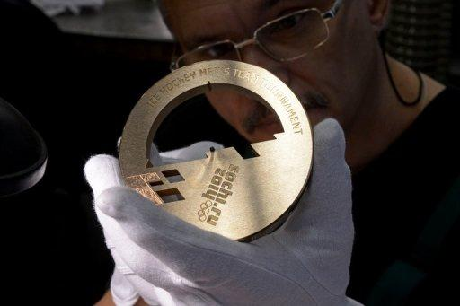 """An employee works on a bronze medal for the 2014 Winter Olympic Games in Sochi, at the Adamas jewellery factory in Moscow on July 25, 2013.Tajikistan may be the poorest of the five former Soviet Republics known as the """"Stans"""" but that does not stop the landlocked Central Asian country from dreaming big, even on the sporting front"""