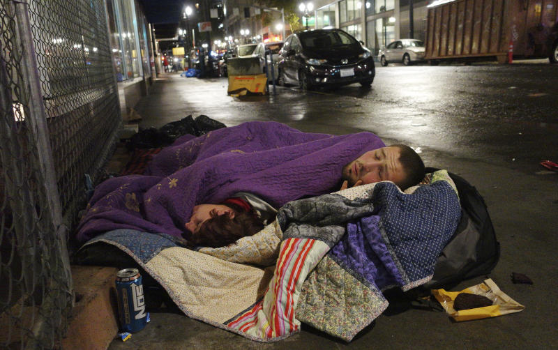 FILE - In this Sept. 18, 2017, file photo, two people sleep on a street in downtown Portland, Ore. A measure to tax the incomes of the wealthiest residents and the profits of the biggest businesses to raise $2.5 billion over a decade to address the homeless crisis sailed to victory in the Portland, Oregon metropolitan region even as the state faces crippling revenue losses and record-high unemployment. Nearly 60% of voters in the three counties that make up the greater Portland region approved the tax amid a greatest economic turmoil in years, a sign of just how intractable the homeless problem has become in the liberal Pacific Northwest city. (AP Photo/Ted S. Warren, File)