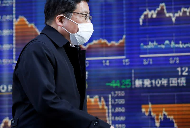A passerby wearing a protective face mask, following an outbreak of the coronavirus, walks past an electronic board showing the graphs of the recent movements of Japan's Nikkei share average outside a brokerage in Tokyo