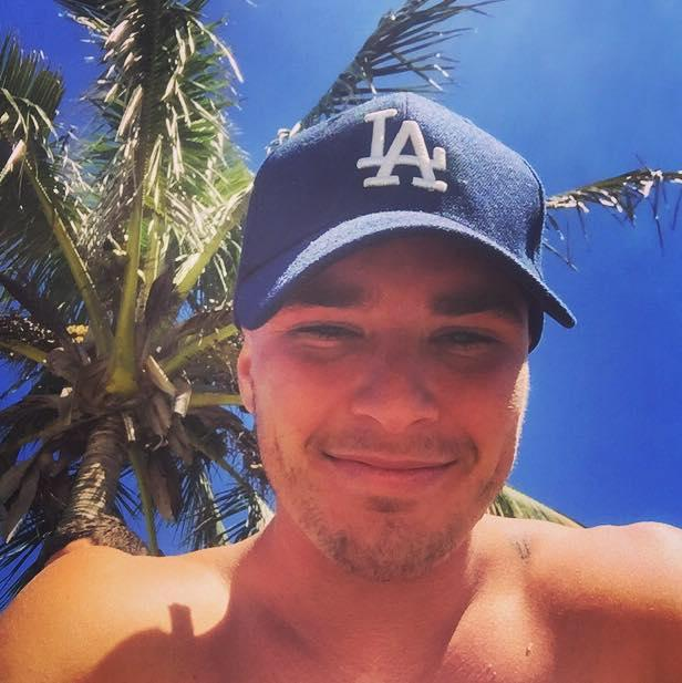 Luke Hansen smiling under a palm tree.