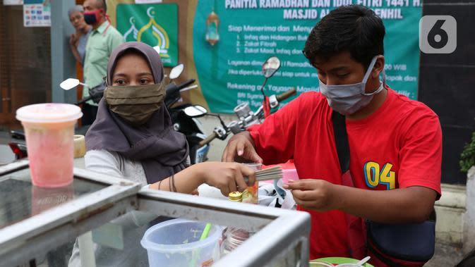 Pedagang menyiapkan minuman untuk berbuka puasa di kawasan Bendungan Hilir, Jakarta, Sabtu (25/4/2020). Meski ditengah pandemi virus Covid-19, masyarakat masih antusias berburu penganan berbuka puasa dengan tetap menerapkan pola jaga jarak dan memakai masker. (Liputan6.com/Helmi Fithriansyah)