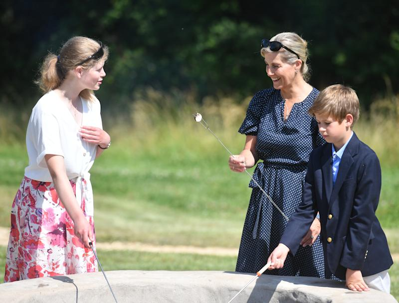 Sophie, Countess of Wessex (centre), with her children, Lady Louise and James, Viscount Severn, toasting marshmallows during a visit to Bear Wood at Wild Place Project in Bristol.