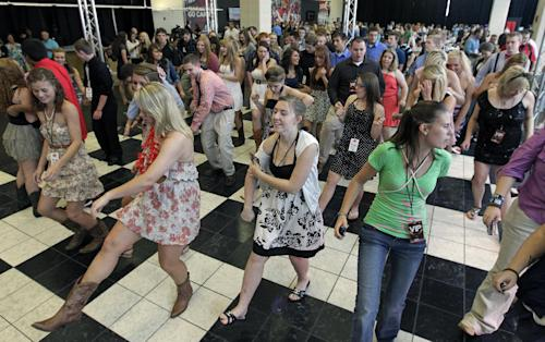 "Students from Henryville High School dance before a concert by Lady Antebellum on Wednesday, May 16, 2012, in Louisville, Ky. Grammy-winning Lady Antebellum trio will stage a ""mini-prom"" bash for students from Henryville Junior-Senior High School, followed by a benefit for the devastated community. (AP Photo/Darron Cummings)"