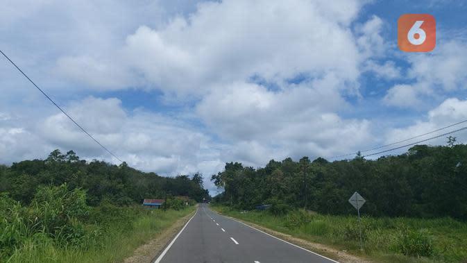 Langit biru dengan awan putih yang tebal serta pepohonan di kanan dan kiri jalan menemani perjalanan rombongan BKKBN dari Pontianan menuju PLBN Entikong, Kalimantan Barat (Foto: Aditya Eka Prawira/Liputan6.com)