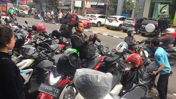 Petugas memarkirkan kendaraan secara manual di sepanjang Jalan Sabang, Jakarta, Jumat (15/12). Karena berakhirnya kontrak, penarikan biaya parkir di 3 wilayah di Jakarta kembali dilakukan secara manual. (Liputan6.com/Immanuel Antonius)