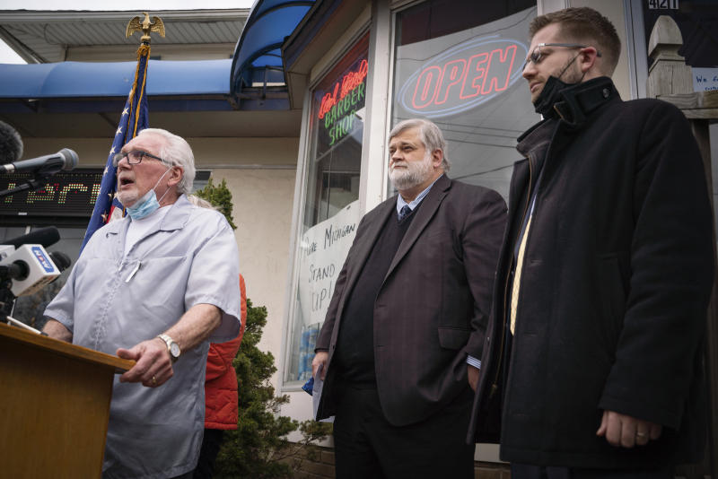 Karl Manke, 77, left, speaks during a press conference alongside his attorney David A. Kallman on Monday, May 11, 2020 at Karl Manke's Beauty & Barber Shop in Owosso, Mich. Manke has defied the governor's order not to conduct business. (Sarahbeth Maney/The Flint Journal via AP)