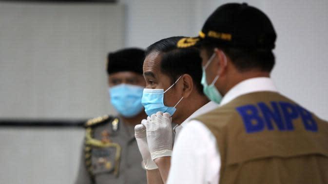 Presiden Joko Widodo mengenakan masker saat meninjau ruang perawatan Rumah Sakit Darurat Penanganan Covid-19 Wisma Atlet Kemayoran, Jakarta, Senin (23/3/2020). Jokowi memastikan bahwa rumah sakit darurat ini siap digunakan untuk karantina dan perawatan pasien Covid-19. (Kompas/Heru Sri Kumoro/Pool)